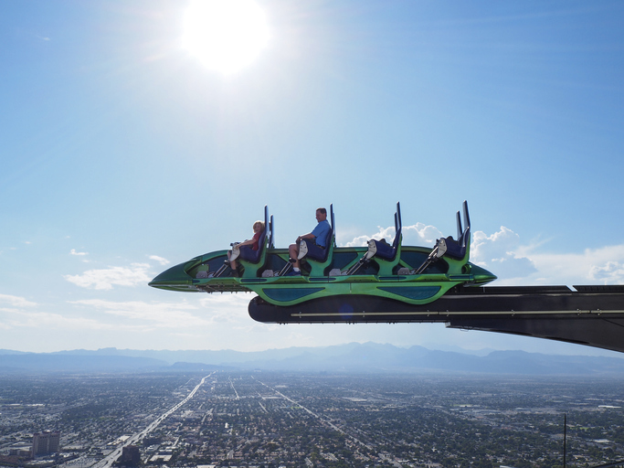 """Tourists sit inside a cart of the thrill ride """"X-Scream"""" on top of the Las Vegas Stratosphere tower (1149 ft/350m), the tallest freestanding observation tower of the US - things to do in Las Vegas"""