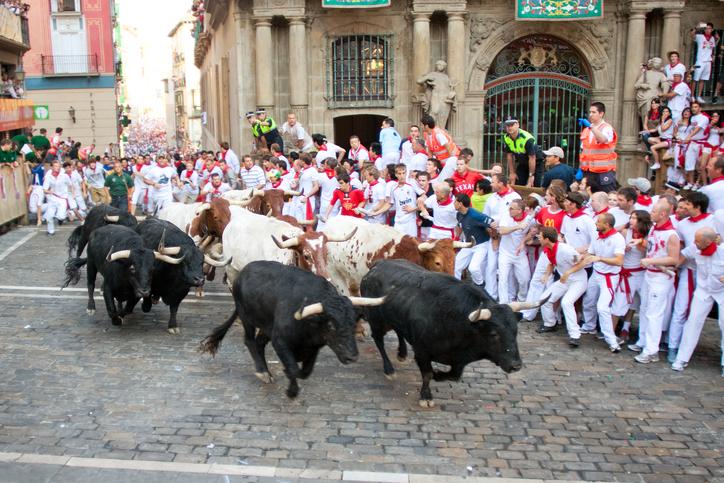 Pamplona. Spain - July 9, 2013: People run from bulls on street during San Fermin festival in Pamplona