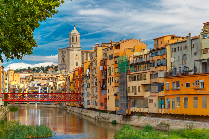 Colorful yellow and orange houses and Eiffel Bridge, Old fish stalls, reflected in water river Onyar, in Girona, Catalonia, Spain. Saint Mary Cathedral at background.