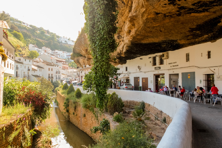 Setenil de las Bodegas, Spain - 5/10/18: Buildings constructed under big rock natural formations in Setenil de las Bodegas. Houses and shops are carved into the rock, providing natural cooling.