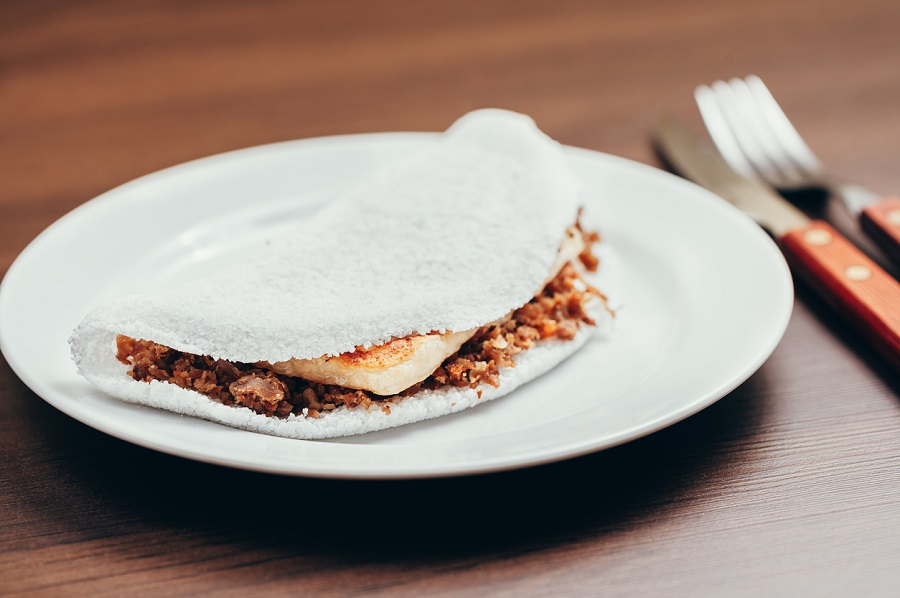Brazilian Tapioca with cheese (coalho) over a wooden table
