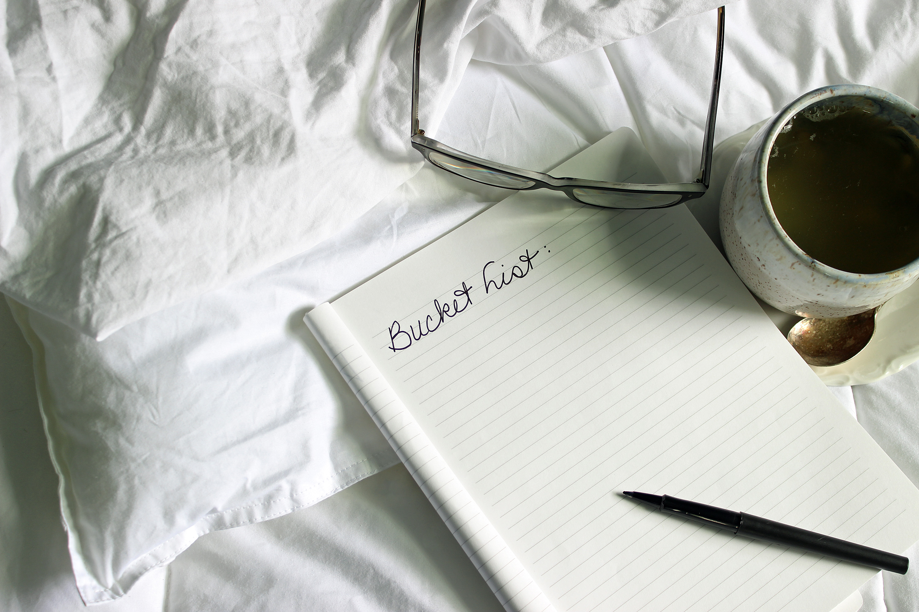 """Bucket List"" printed on blank notebook, eyeglasses, cup of tea in white unmade bed."