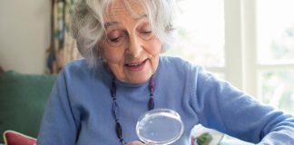 Senior Woman At Home Reading Book Using Magnifying Glass, Senior Travel