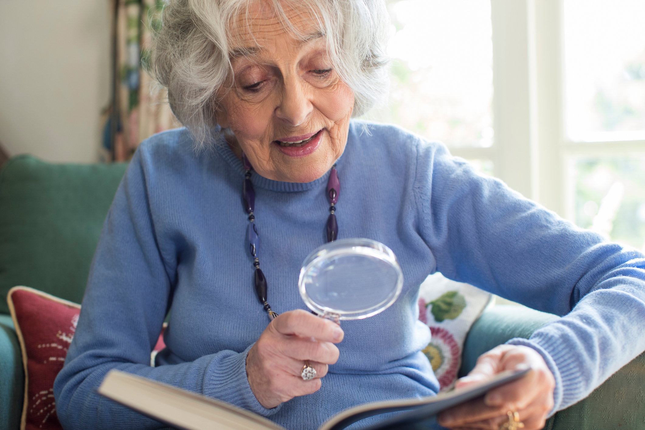 Senior Woman At Home Reading Book Using Magnifying Glass