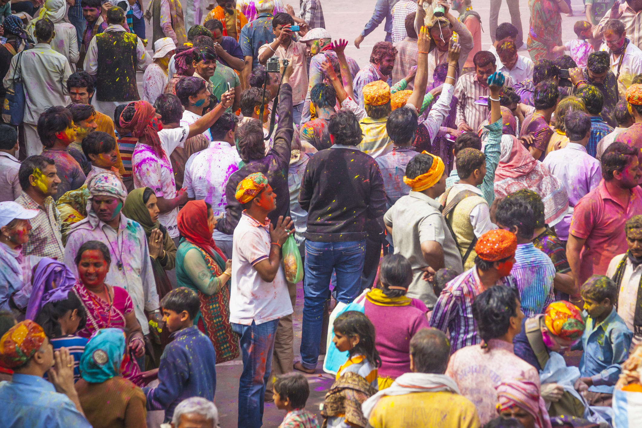 People praying and celebrating Holi near the Mathura temple.