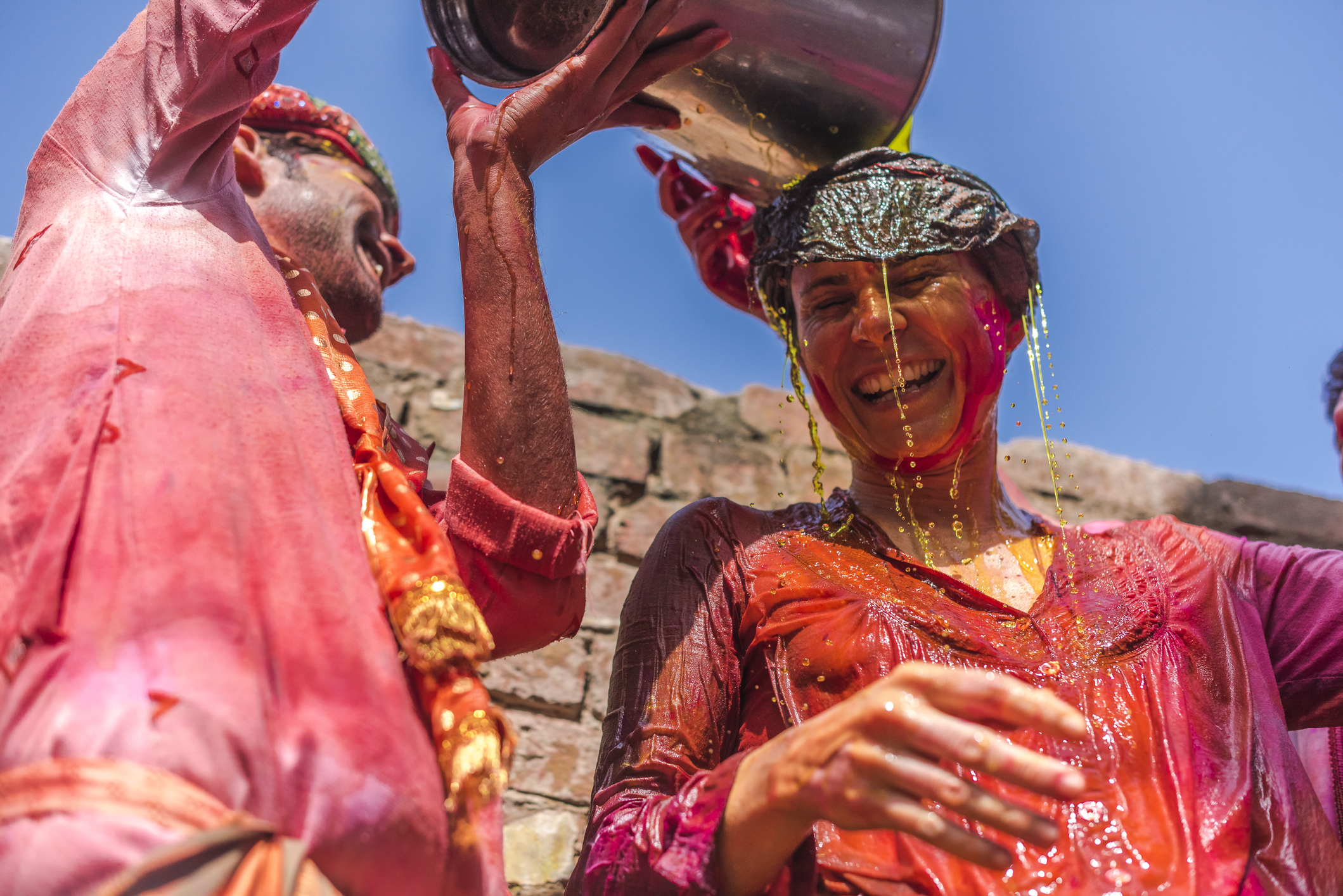 Barsana, India - February 28, 2015: Villagers of barsana celebrating holi festival full of water colours with foreign tourists at village barsana, Uttar Pradesh, India.
