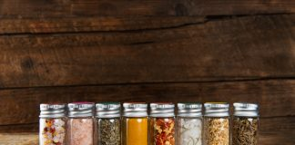 Spices Set in Mini Bottles, such as basil, turmeric, salts, chilli flakes, cumin seeds on dark wooden background