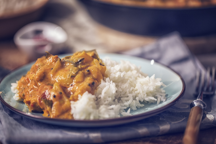 Delicious homemade chicken curry dish with basmati rice served on a plate.