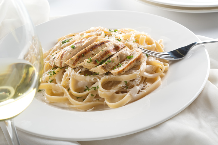Delicious grilled chicken alfredo with fettuccine, grated parmigiano reggiano, and chopped parsley garnish.