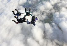 Four skydivers in freefall over clouds