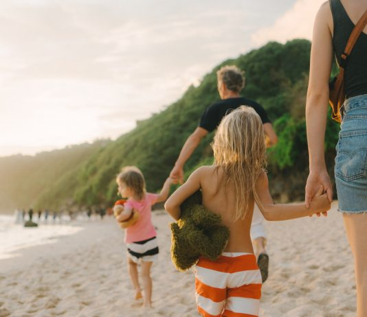 Caucasian family with two daughters walking on the beach in Bali, Indonesia Bali with kids