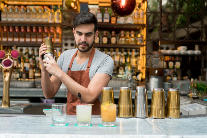 Happy Latin American male bartender making cocktails at a bar budget trips