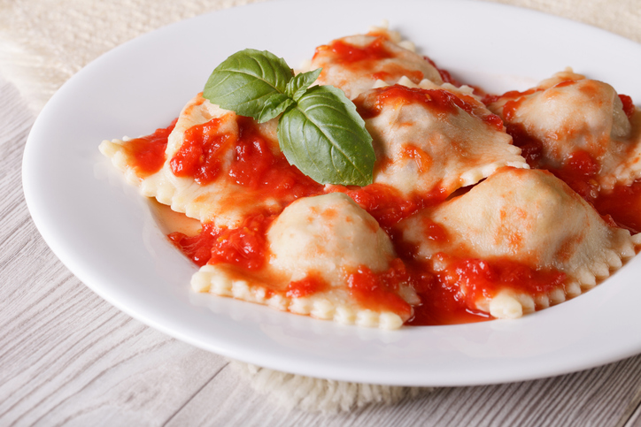 Ravioli stuffed with meat in tomato sauce on a plate close-up. horizontal