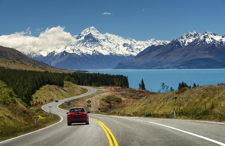 Red car going to the beautiful landscape lake tekapo, Mt.cook, Lupines fields, South island New Zealand