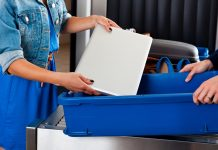 Close up of woman's hands putting a laptop into a container at airport security checkpoint. us airports