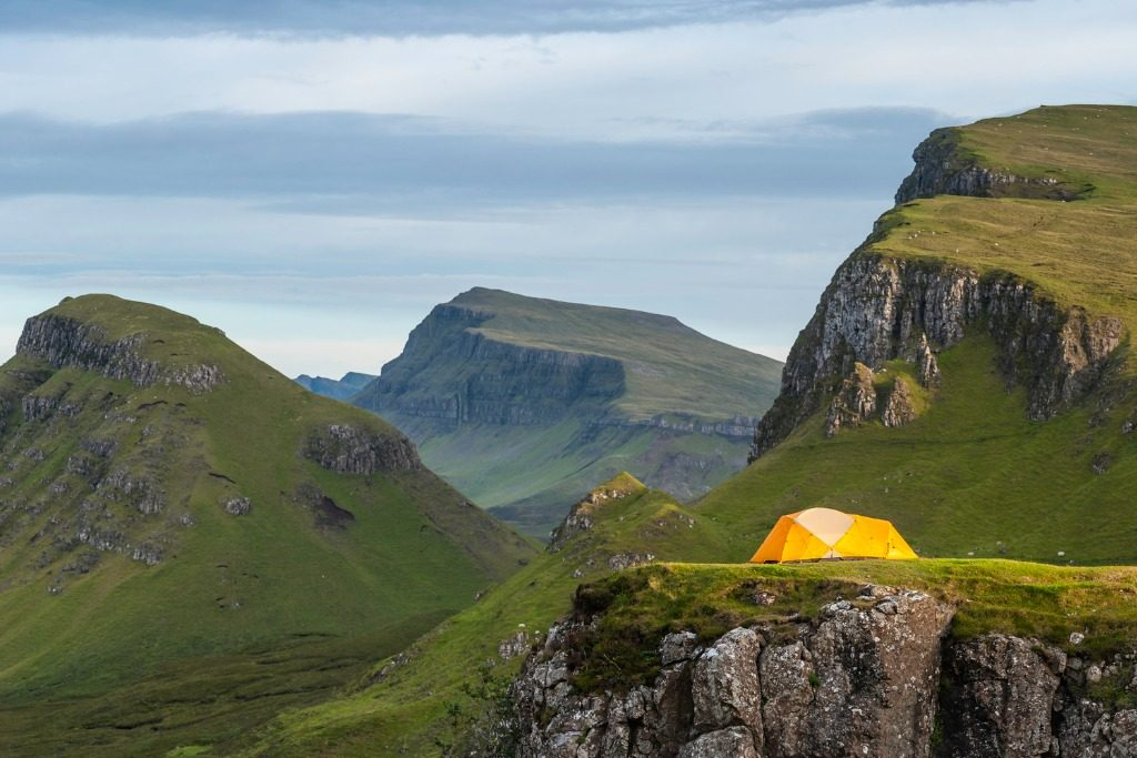 Yellow dome tent in dramatic mountain wilderness Highlands Scotland travel tips
