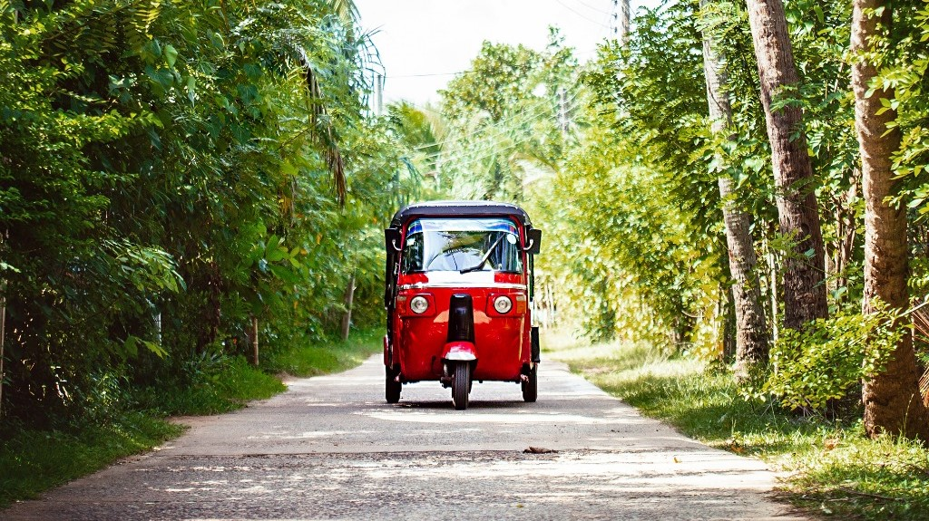 Red tuk-tuk under the palm trees on the country road in Weligama, Sri Lanka