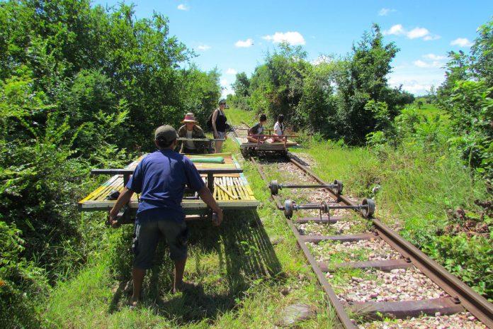 tourists doing Bamboo train in Cambodia