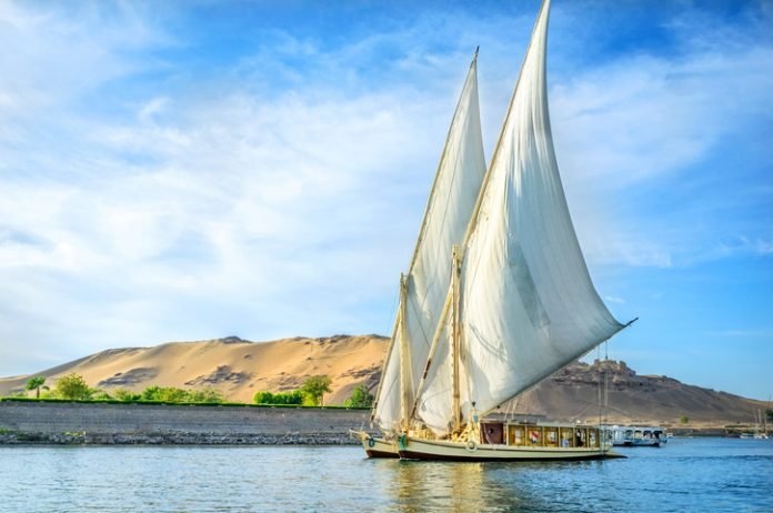 A traditional boat sailing through the Nile River in a late afternoon in Egypt