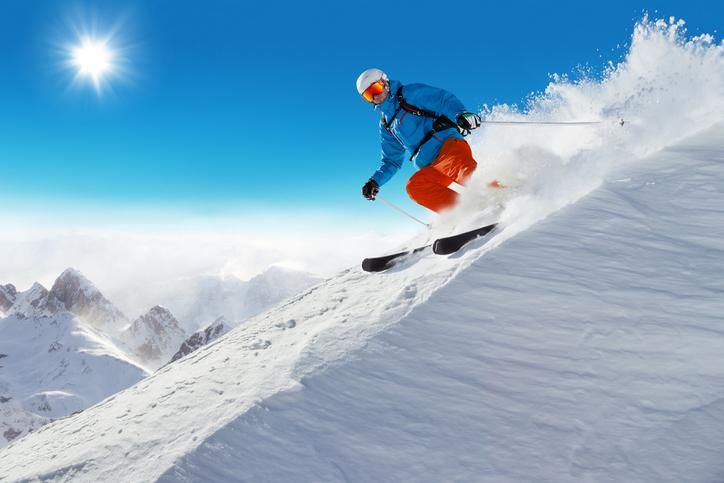 Man skier running downhill on sunny Alps slope Kufri