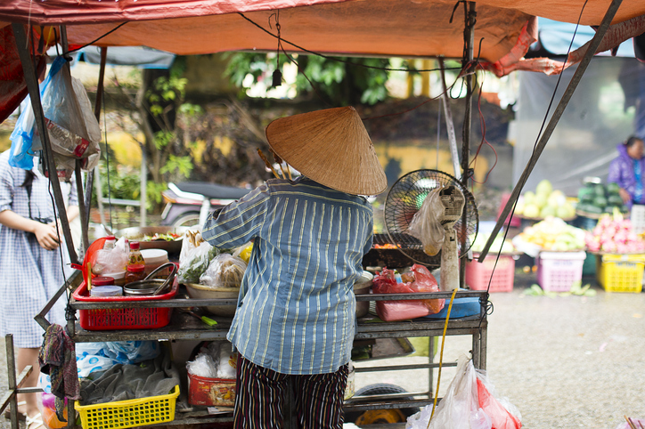 Unidentified woman with a typical Vietnamese conical hat sells roast beef on a street market in Hoi An, Vietnam.