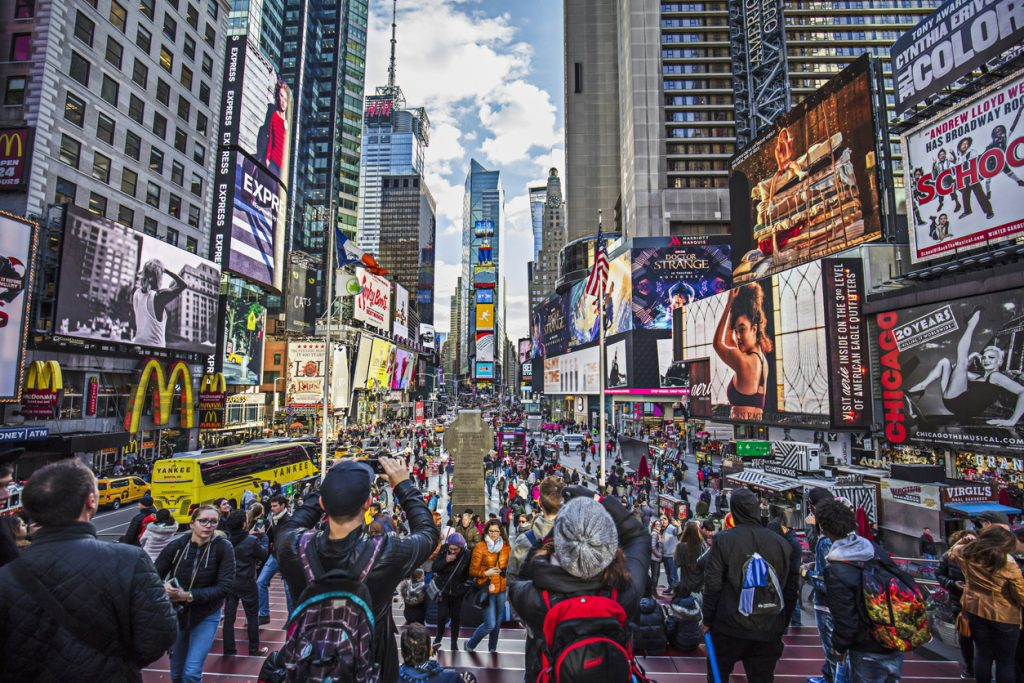 View of crowded Times Square in New York City, hypersonic jet