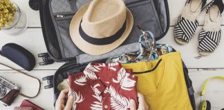 Woman hand preparing summer luggage pack light