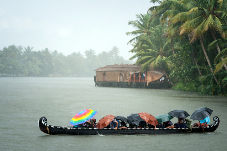Monsoon time. People crossing a river by boat in rain with umbrellas. india travel tips