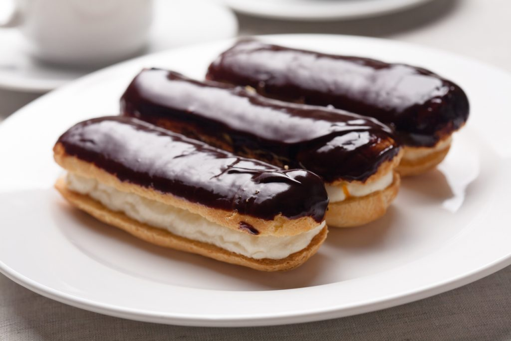 Chocolate eclairs on plate on white background