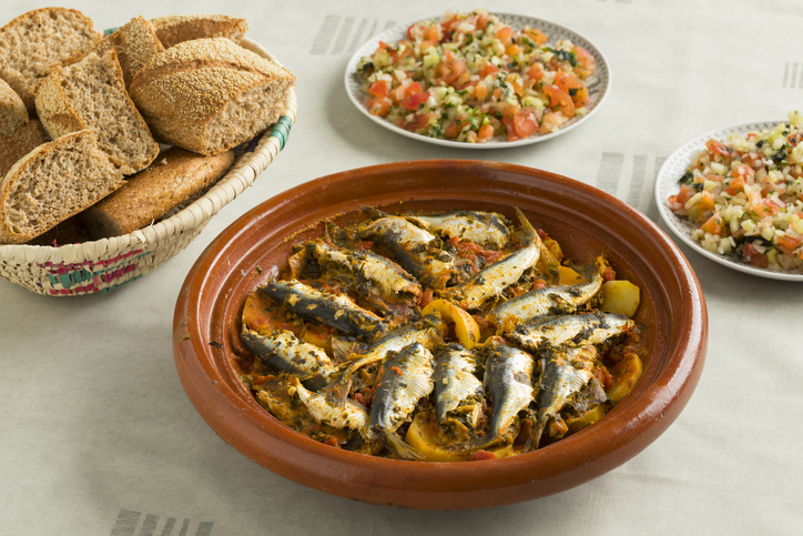 Traditional Moroccan dish with sardines and vegetables, salad and a basket with bread