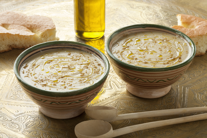 Bowls with Moroccan bessara soup, olive oil and cumin