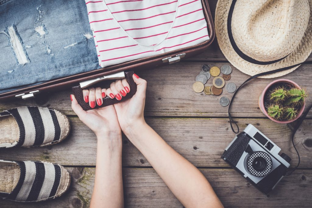 Travel preparations concept with suitcase, clothes and accessories on an old wooden table. Zero waste travel