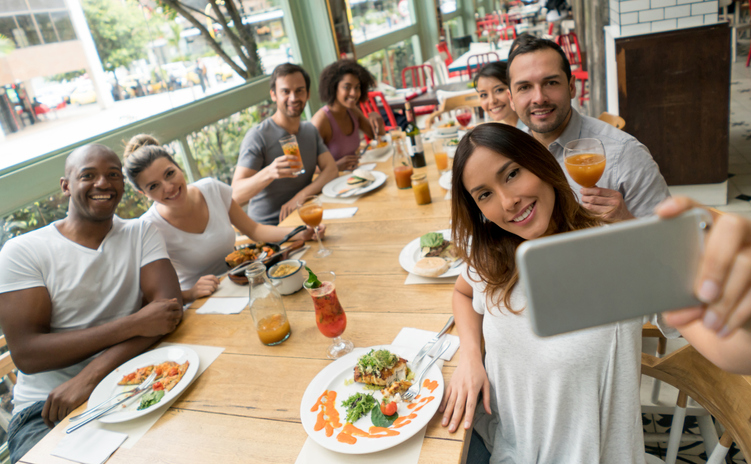 Happy group of friends taking a selfie at a restaurant while having dinner together