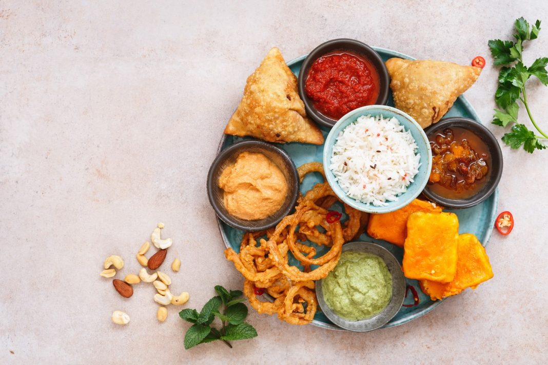 Indian vegetarian thali with jeera rice, different snacks and dips