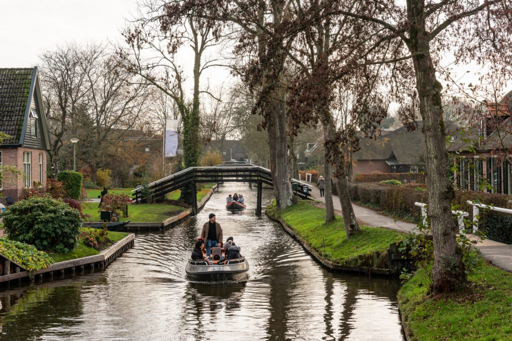 Beautiful green winter scene of people in two small boats cruising on narrow canals among buildings in the famous village Giethoorn Netherlands.