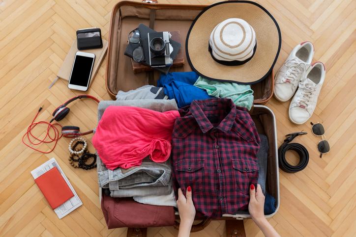 Woman hand preparing summer luggage travel bag