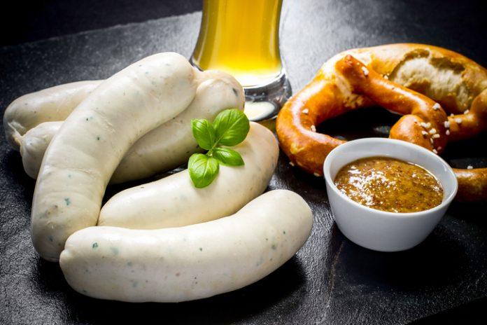 Original Munich sausage with Hefeweizen and pretzel on black slate plate