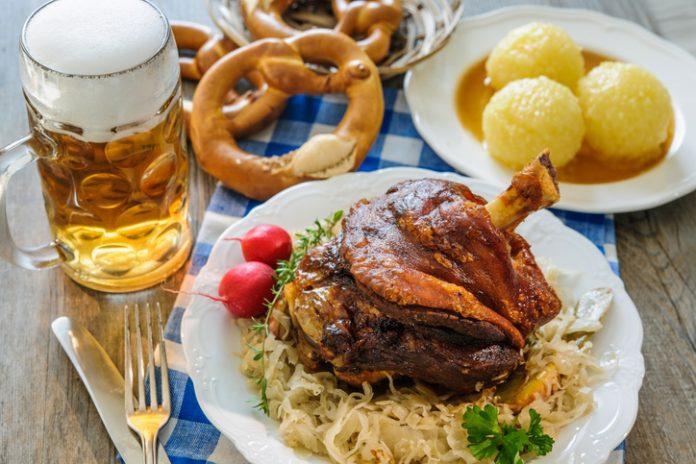Appetizing Bavarian roast pork knuckle with dumplings and sauerkraut. Oktoberfest