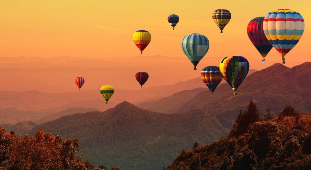 Hot air balloon above high mountain at sunset, Kenya