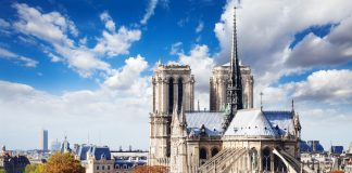 Notre Dame cathedral in Paris with panorama of Paris on background view from the roof of house on Siena