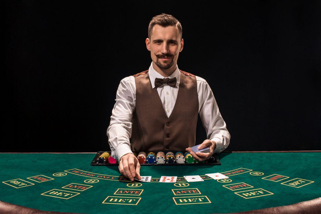 Portrait d'un croupier tient des cartes à jouer, des jetons de jeu sur la table.  Fond noir.  Un jeune homme croupier en chemise, gilet et nœud papillon vous attend à la table de blackjack