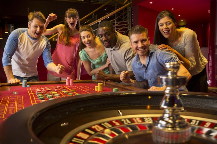 Group Of Friends Playing Roulette In Casino