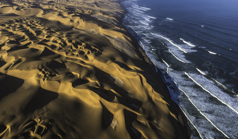 Aerial view of the sand dunes of the Namib Desert colliding with the Atlantic Ocean, Namibia.
