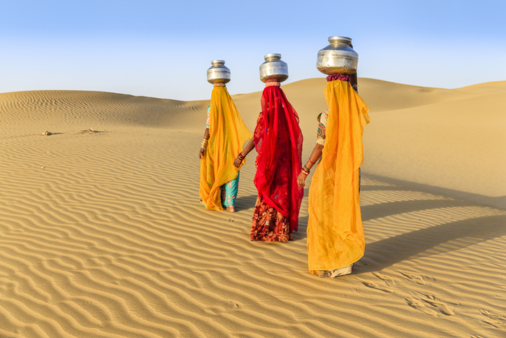 Indian women crossing sand dunes and carrying on their heads water from local well, Thar Desert, Rajasthan, India. Rajasthani women and children often walk long distances through the desert to bring back jugs of water that they carry on their heads.