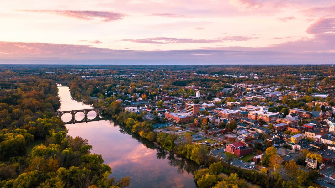 An aerial view of Fredericksburg, Virginia with the Rappahannock River in the foreground and the downtown area visible beyond at sunrise.