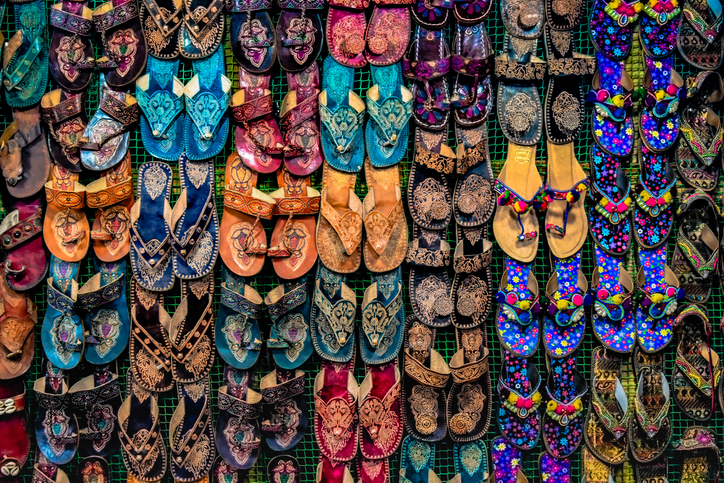 Kolhapuri Chappal- Colorful and variety of Ladies Ethnic Footwear displayed on sale at the street market in India. Kolhapuri Chappal in India are usua