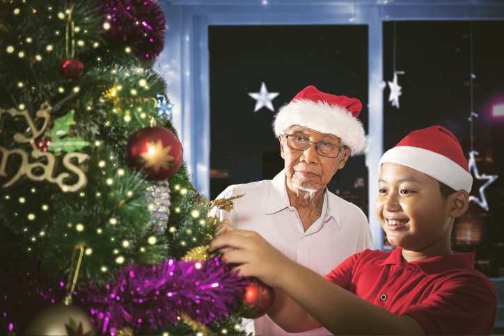 Image of old man and his grandson decorating a tree to prepare Christmas day. Shot at home