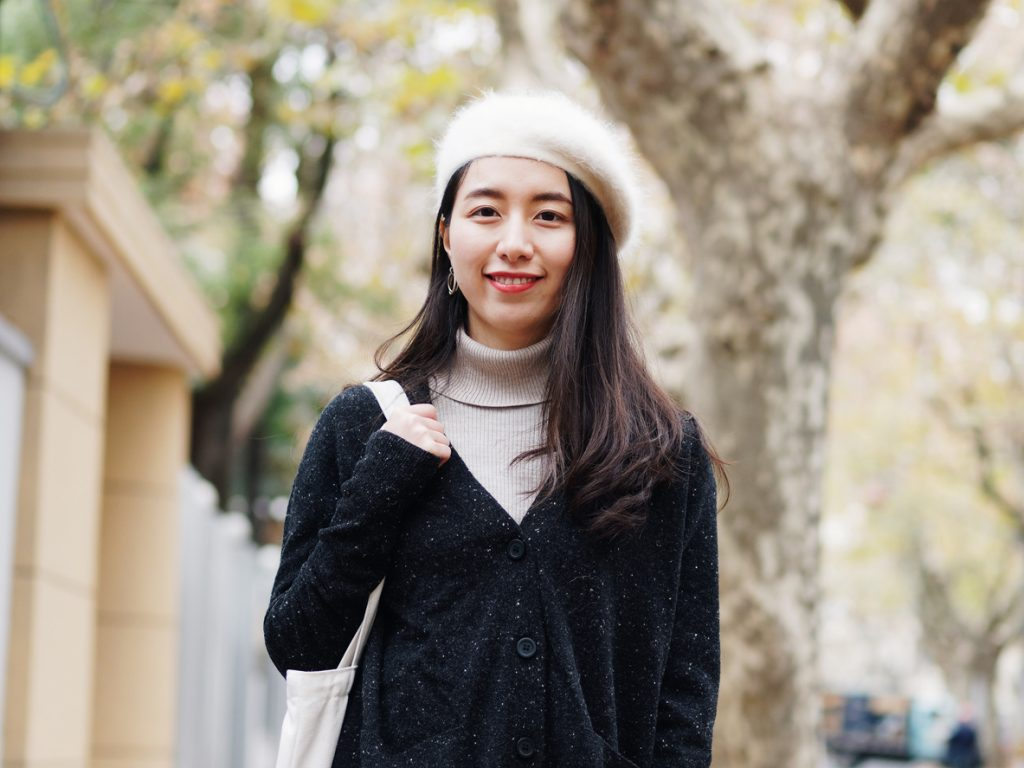 Beautiful young brunette woman in white beret and black woolen sweater smiling at camera with blur street background. Outdoor fashion portrait of glamour young Chinese cheerful stylish lady.
