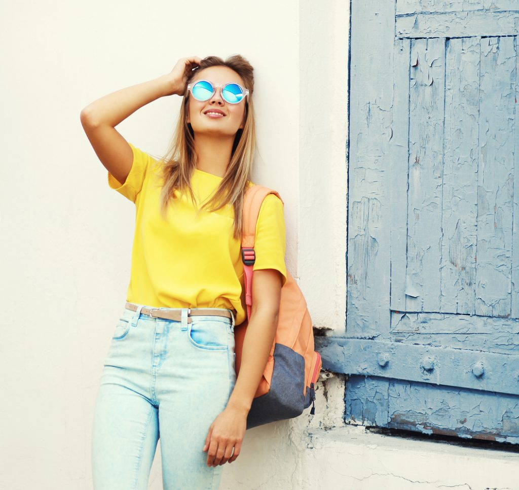 Pretty blonde young woman wearing a sunglasses and yellow t-shirt in the city, street fashion