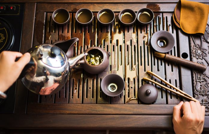 Woman traditionally preparing Chinese tea in a traditional Tea ceremony